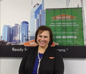 SERVPRO of Jersey City shares picture of one of their female project managers smiling and standing in front of a SERVPRO Ad.