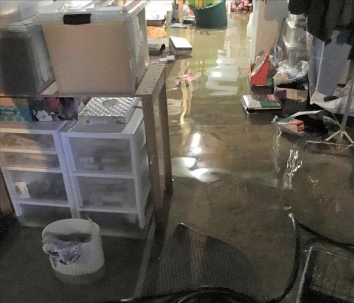 A flooded concrete floor in a basement room